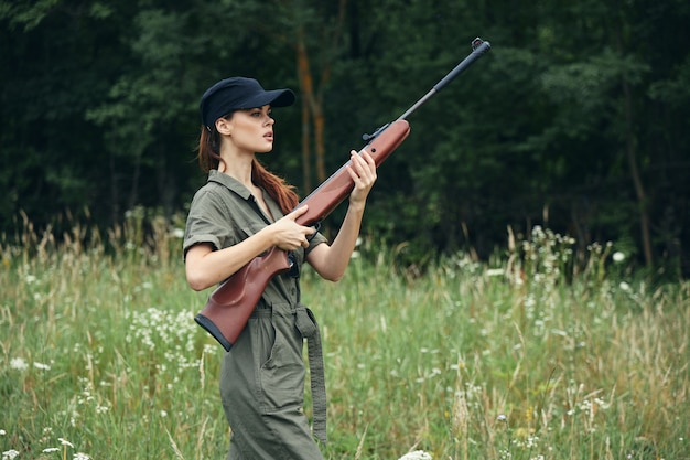 Woman holding a weapon in hands wearing green jumpsuit