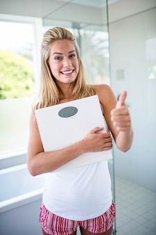 Woman holding a weighting scale with thumbs up in the bathroom