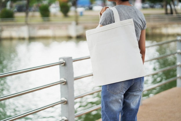 Woman holding white blank tote bag