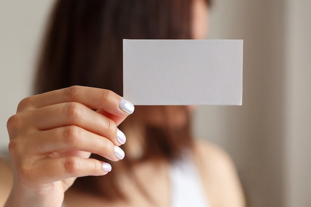 Woman holding a white business card in his hand, close up. empty space for text
