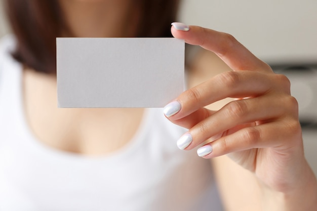 Woman holding a white business card in his hand, close up