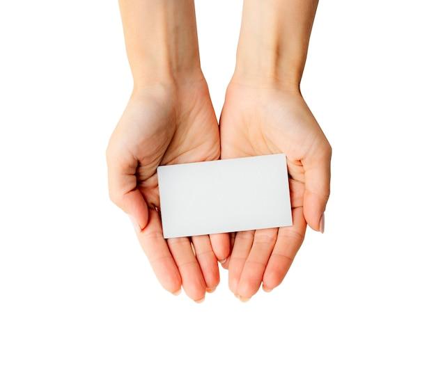 白い背景で隔離の手で白い名刺を保持している女性。あなたのデザインのためのタンプレート。