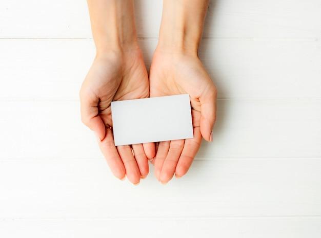 手に白い名刺を持っている女性。あなたのデザインのためのタンプレート。
