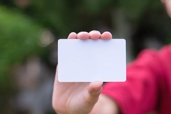 Woman holding white business card on natural bokeh background