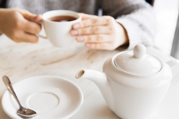 Woman holding white cup of tea in hands. breakfast on white table in the cafe