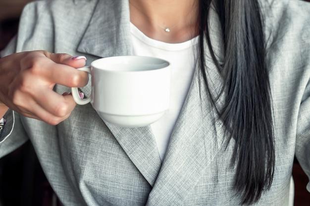Женщина, держащая белую чашку.