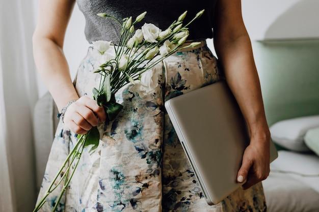 흰색 lisianthus와 노트북을 들고 여자