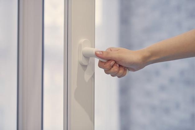 二重ガラス、開閉フレーム付きのpvcプラスチック窓で白いモダンなハンドルを保持している女性