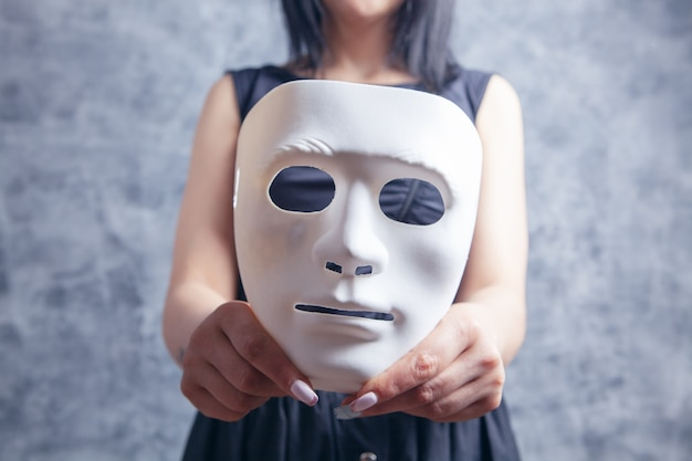 Woman holding white plastic mask on gray background