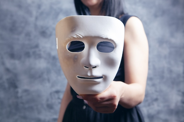Woman holding white plastic mask
