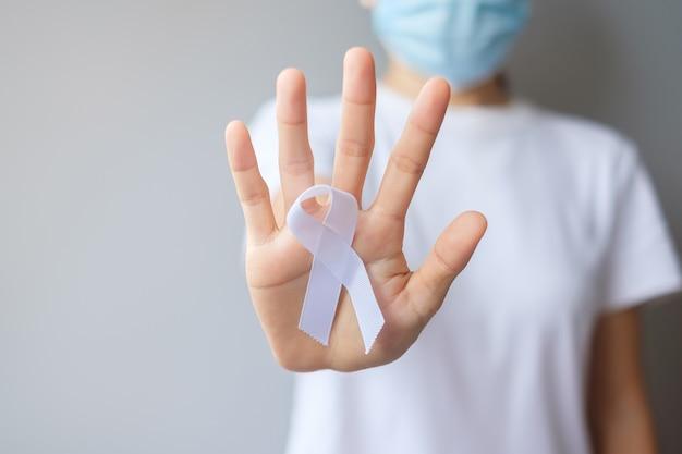 11월 폐암 인식의 달, 민주주의 및 국제 평화의 날을 위해 흰색 리본을 들고 있는 여성. 의료 개념