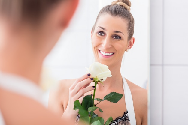 Woman holding white rose regarding herself in the mirror