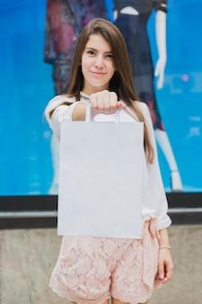 Donna che tiene il sacchetto della spesa bianco vicino alla finestra del negozio