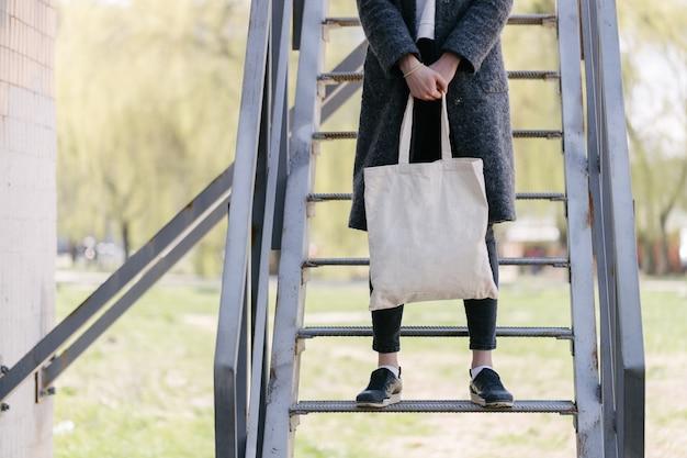 Женщина, держащая белую текстильную эко-сумку в городском районе