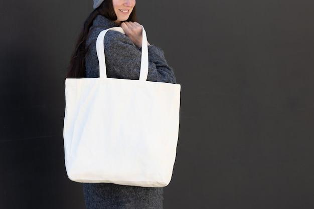 都市部で白いテキスタイルトートエコバッグを保持している女性