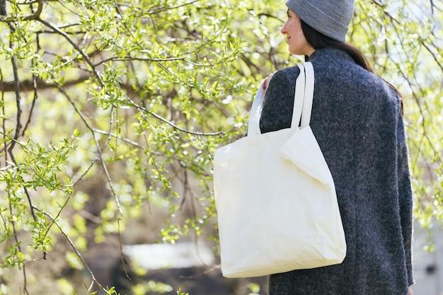 Woman holding white textile tote eco bag in urban area