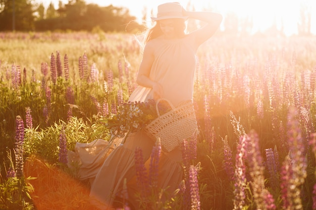 Woman holding wicker bag in her hands wearing fedora hat on sunset in lupine field