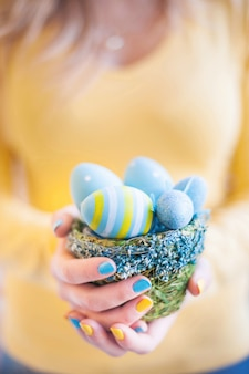 Woman holding a wicker basket of coloured easter eggs