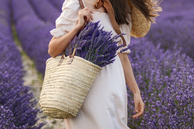 Woman holding wicker basket with a lavender in the field
