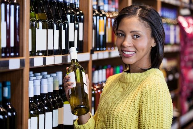 Женщина держит бутылку вина в продуктовом разделе