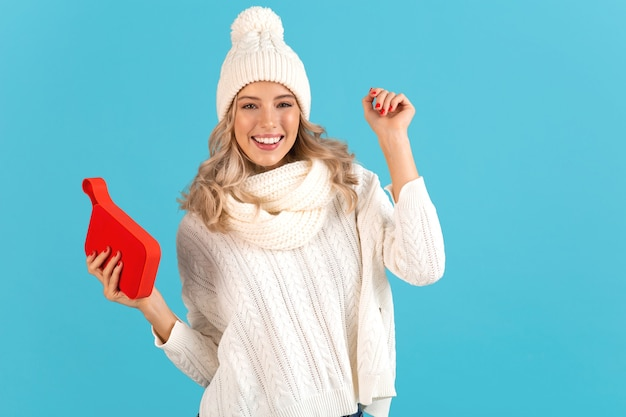 Donna che mantiene l'altoparlante wireless ascoltando musica felice ballare indossando un maglione bianco e berretto lavorato a maglia in posa isolato su blue