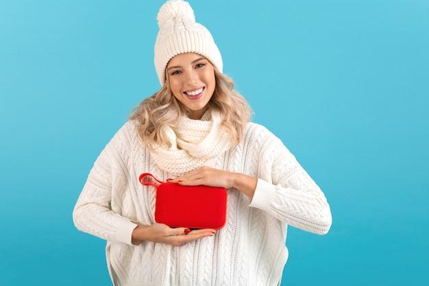 Donna che mantiene l'altoparlante wireless ascoltando musica felice indossando un maglione bianco e berretto lavorato a maglia in posa isolato su blue