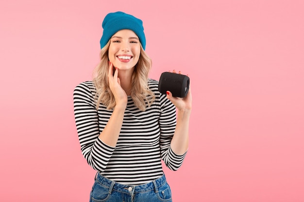 ストライプのシャツと青い帽子を身に着けている音楽を聞いているワイヤレススピーカーを持っている女性はピンクでポーズをとって幸せな前向きな気分を笑っています