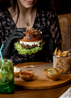 Woman holding with black gloves beef burger with mushroom, lettuce and cheese