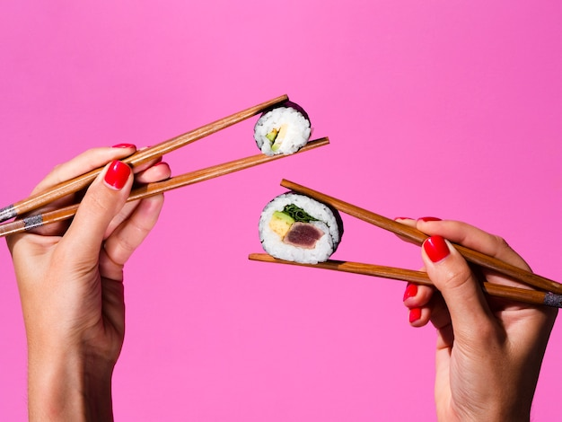 Woman holding with both hand sushi rolls on chopsticks