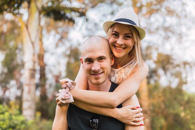 彼氏を後ろから愛情を込めて抱きしめ、カメラに向かってポーズをとる女性