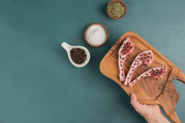 Donna che mantiene la tavola di legno di pezzi di carne cruda.