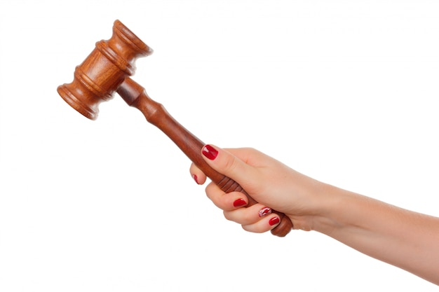 Woman holding wooden gavel in her fist isolated on white