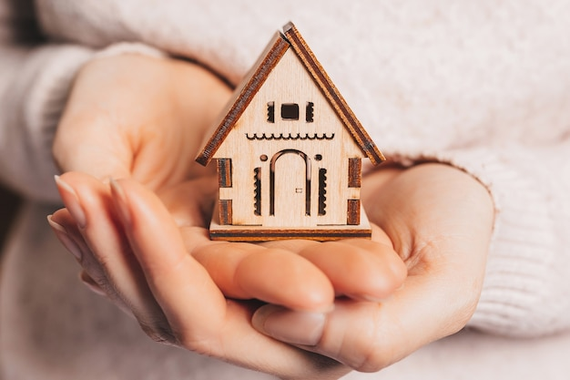 Woman holding a wooden house with her hands