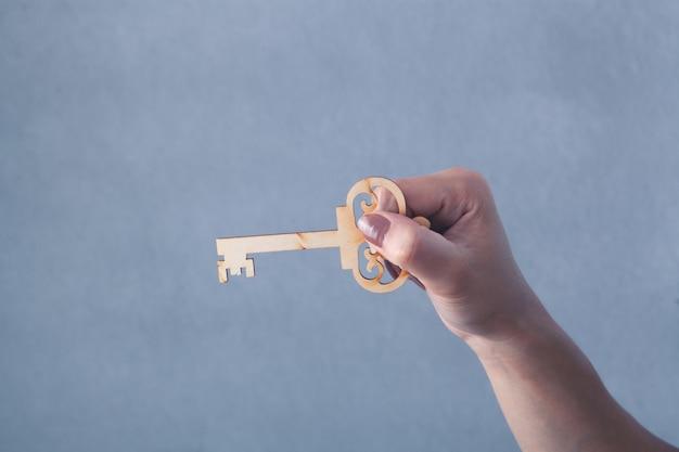 Женщина держит деревянные ключи на сером фоне