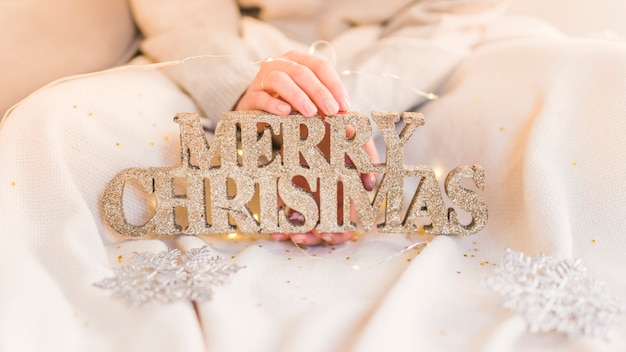 Woman holding wooden merry christmas inscription in hands