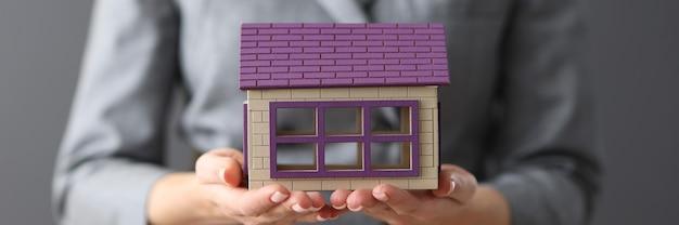 Женщина, держащая деревянный игрушечный домик в ее руках, концепция страхования жилья крупным планом