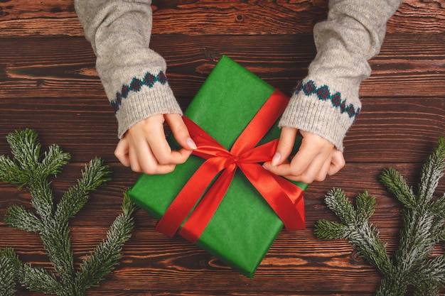 Woman holding wrapped christmas present in her hands, view from above