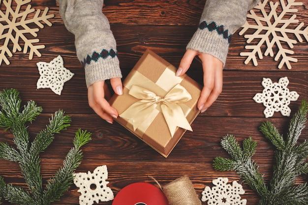 Женщина, держащая обернутый рождественский подарок в руках, вид сверху
