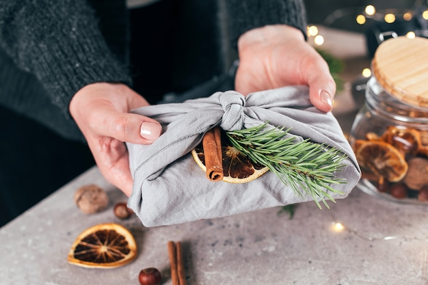 녹색 나뭇가지, 유기농 장식이 있는 직물에 포장된 선물을 들고 있는 여자. 제로 웨이스트 크리스마스.