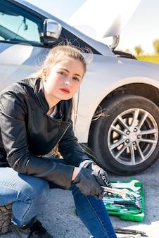 サービスの助けを待っているレンチを保持している女性