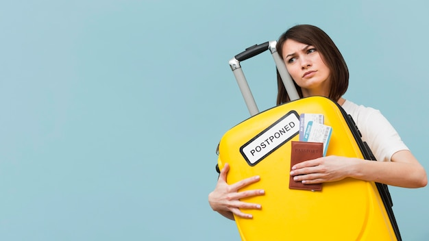Woman holding a yellow baggage with a postponed sign with copy space
