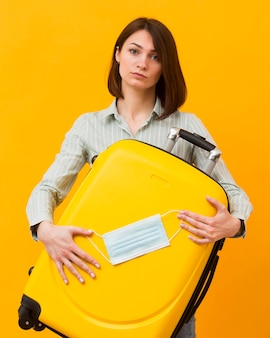 Woman holding a yellow luggage and a medical mask