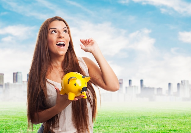 Woman holding yellow moneybox with arm up