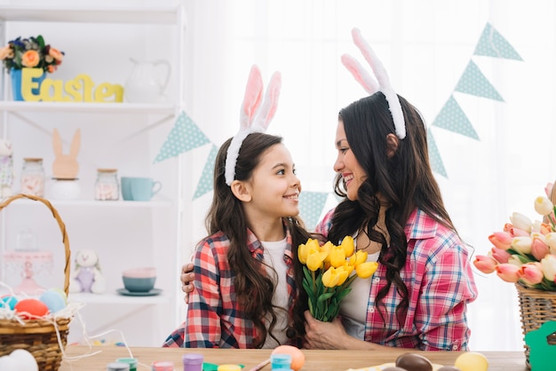 Woman holding yellow tulips bouquet embracing her daughter on easter day celebration