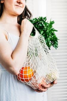 女性は食品の新鮮な野菜や果物の袋を持っています