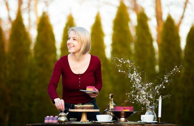 Женщина держит торт во время чаепития в саду
