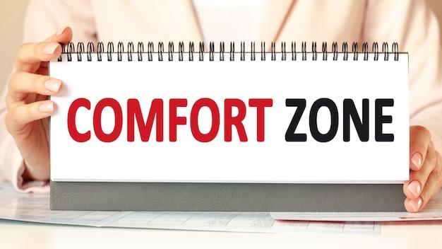 여자 손으로 comfort zone 텍스트와 골 판지를 보유하고있다.