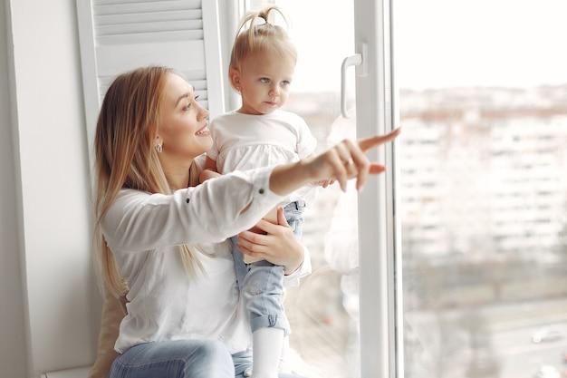女性は子供を腕に抱き、抱きしめます。白いシャツを着たお母さんが娘と遊んでいます。家族は週末に楽しんでいます。