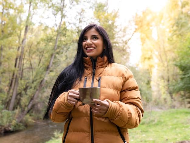 Женщина держит чашку в лесу, осенняя концепция
