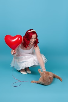 Женщина держит летающий воздушный шар в форме сердца, приседает и играет с рыжим британским котом